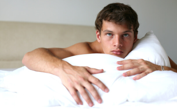 Shirtless man in bed on a pillow