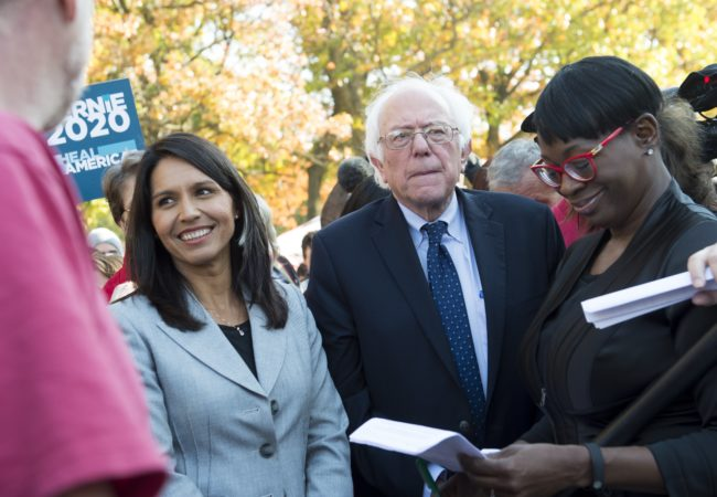 US Senator Bernie Sanders, (I-VT), waits alongside US Representative Tulsi Gabbard (L), Democrat of Hawaii, to speak during a rally to stop the Trans-Pacific Partnership (TPP).