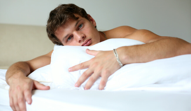 Man in bed with pillow
