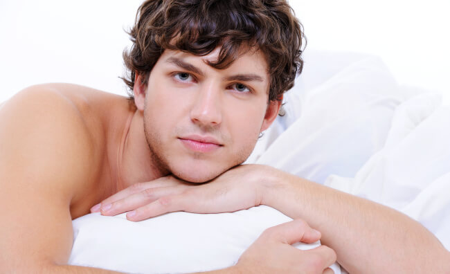 Shirtless man in bed