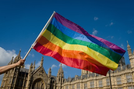 A protester holds a rainbow flag outside the Houses of Parliament in central London on June 3, 2013, as protesters gather in support of same-sex marriage