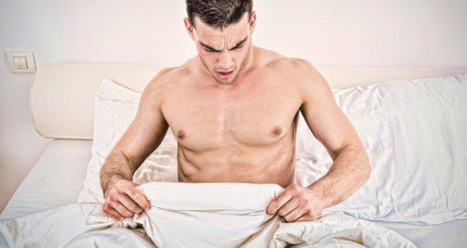 A man looks at his groin in bed - sexual health/STI